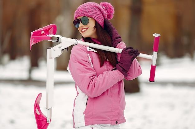 Женщина в зимнем парке. дама в розовом спортивном костюме. женщина с самокатом снега.