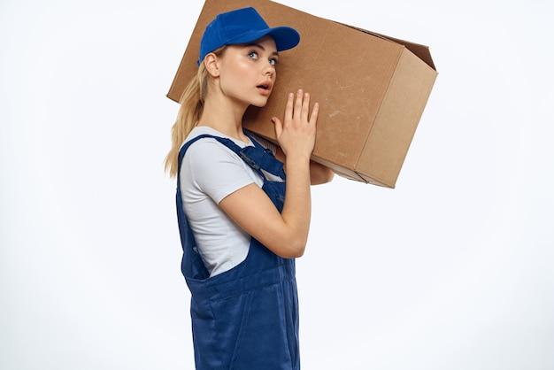 配達サービスの手に箱を持った作業服を着た女性