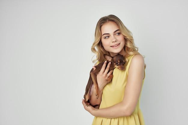 黄色いドレスを着た女性は、小さな犬のクロップドビューファッションを楽しんでいます。高品質の写真
