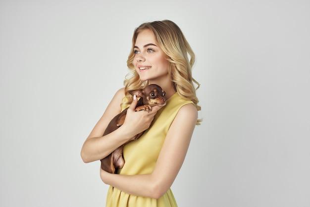 黄色いドレスを着た女性が小さな犬のクロップドビューファッションを楽しんでいます