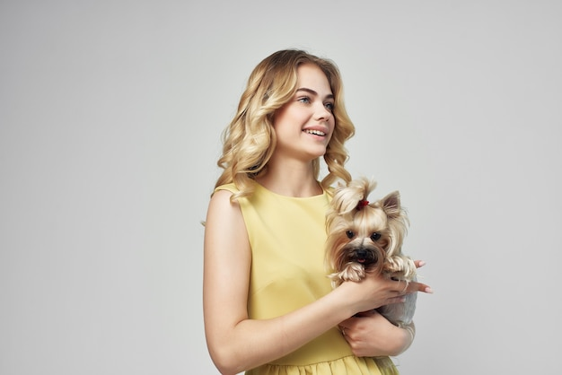 黄色のドレスを着た女性は、小さな犬の孤立した背景を楽しんでいます