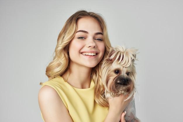 黄色いドレスを着た女性は、小さな犬の明るい背景スタジオを楽しんでいます。高品質の写真