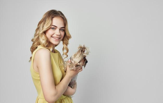 Женщина в желтом платье держит на руках маленькую собачку радость.