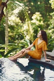 バリ島のプールサイドで座っている黄色のドレスを着た女性