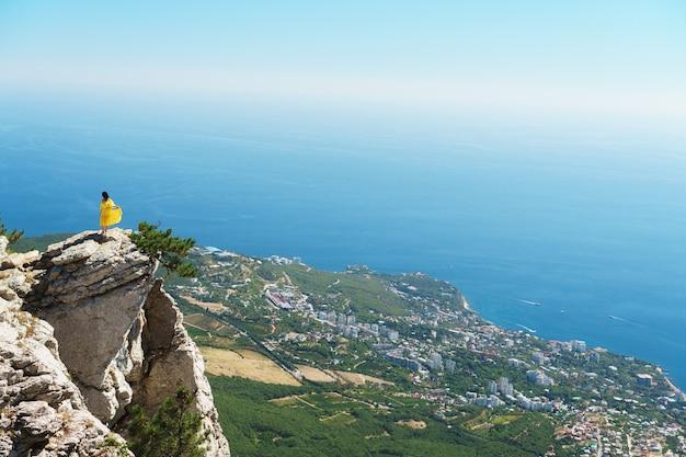 Женщина в желтом платье стоит на скале у обрыва у синего моря.