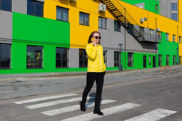 黄色いジャケットを着て、明るい色の建物の背景を持つ携帯電話で話している女性