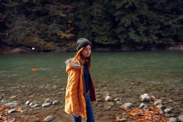 川の近くの黄色いジャケットの女性は自然を賞賛します秋の森