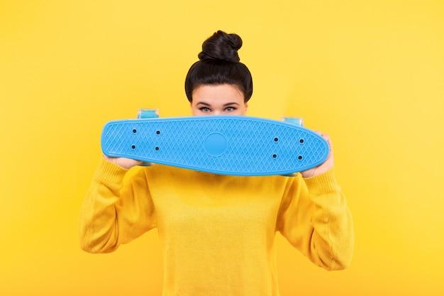 黄色のプルオーバーの女性、青いスケートボードで顔を覆う