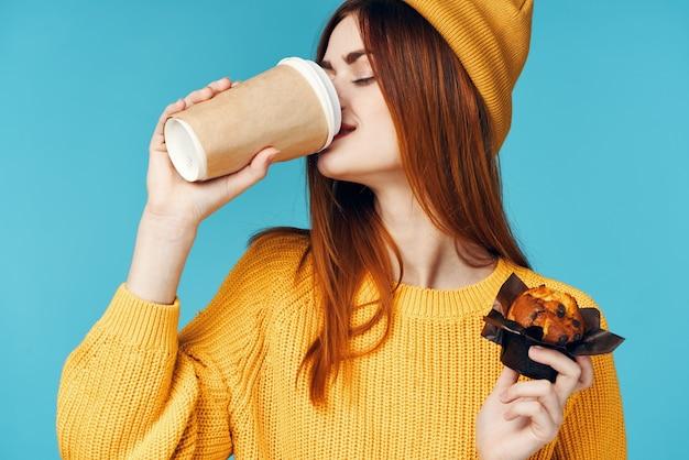 노란색 스웨터와 모자를 쓴 여성이 손에 커피 컵케익 한 잔을 들고 간식을 먹습니다. 고품질 사진