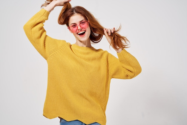 黄色のセーターの髪型の女性ファッションメガネ孤立した背景。高品質の写真