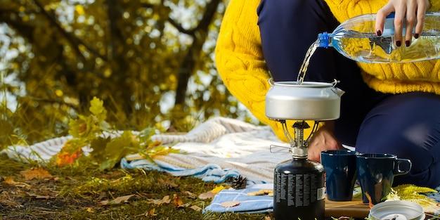 ガスバーナーで森の中でコーヒーを作るために水を注ぐ黄色いセーターの女性。秋の森のプリムスストーブでコーヒーを作る