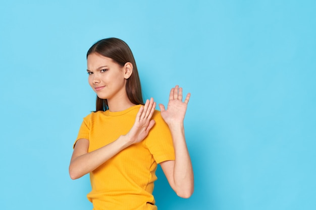 역겨운 노란색 티셔츠를 입은 여성이 옆으로 몸을 돌리고 파란색에 손을 대고 몸짓을 한다