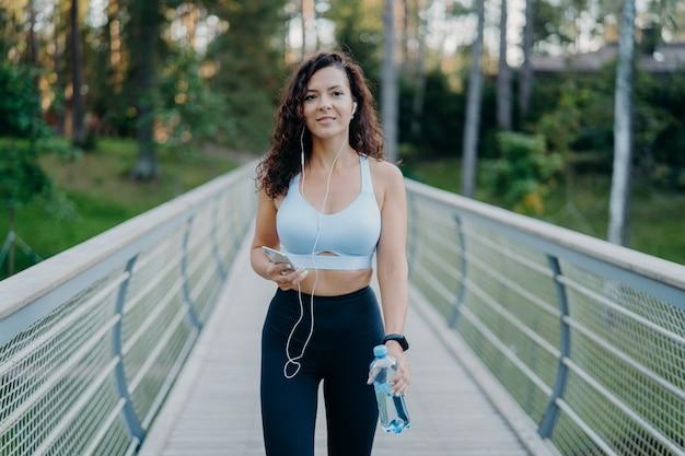 アクティブウェアの女性が森の近くでジョギングをし、イヤホンで音楽を聴くのを楽しんでいます