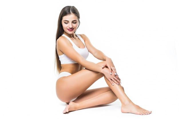 Женщина в активной одежде сидит на полу, изолированных на белой стене