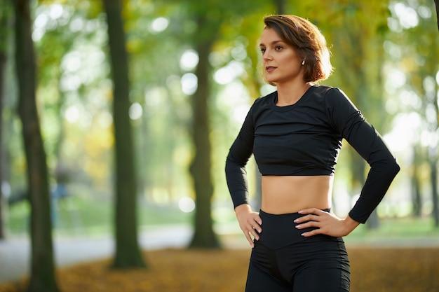 Женщина в спортивной одежде расслабляется между упражнениями в парке