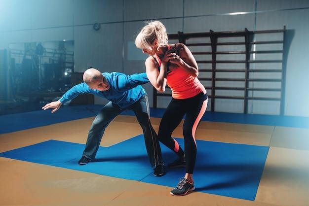 Женщина в действии на тренировках по самообороне с личным инструктором, боевые тренировки в тренажерном зале, боевые искусства