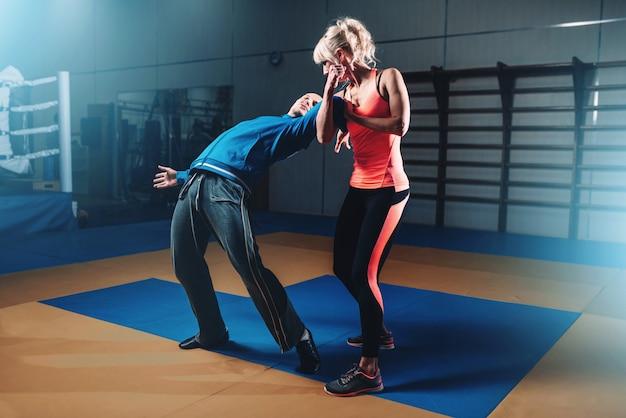 Женщина в действии на тренировке по самообороне