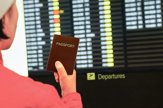 그녀의 손에 여권을 들고 공항에서 여자, 비행 정보 보드를보고