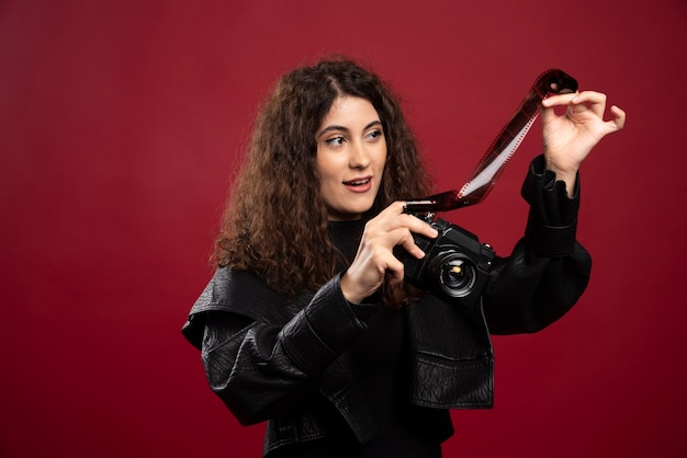 Женщина во всем черном наряде держит фотоленту с фотоаппаратом.