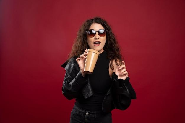 Женщина в черном наряде позирует с чашкой и очками.