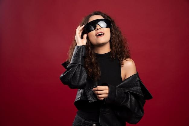 검은 안경을 쓰고 모든 검은 옷을 입은 여자.