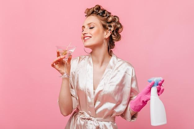 Женщина в легком халате держит чистящее средство и наслаждается бокалом мартини