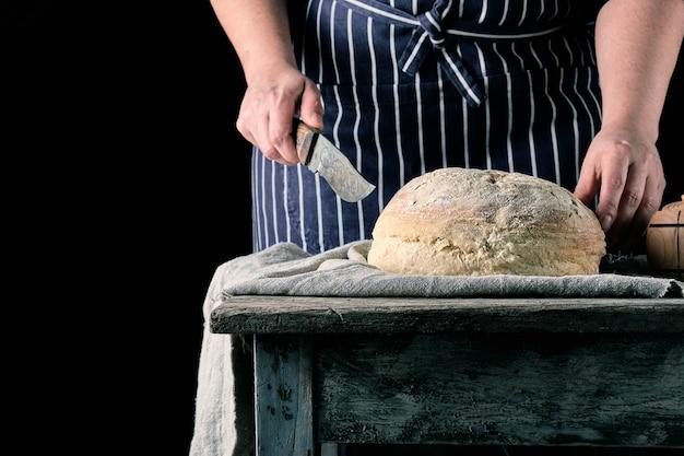 라운드 구운 빵을 잘라하려고 그녀의 손에 칼으로 앞치마에 여자