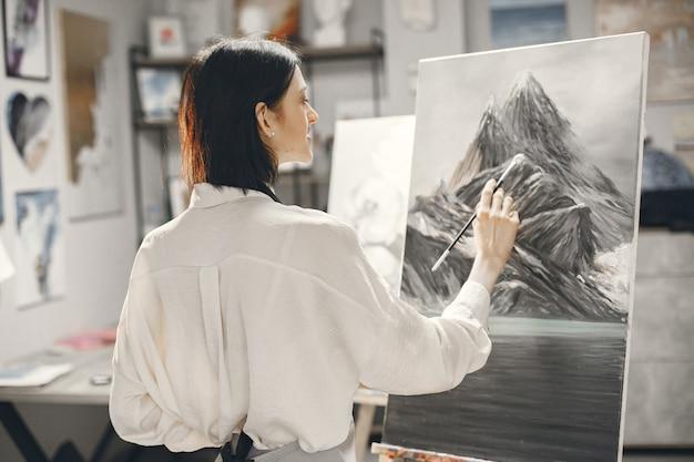 Женщина в художественной школе в фартуке рисует на мольберте.