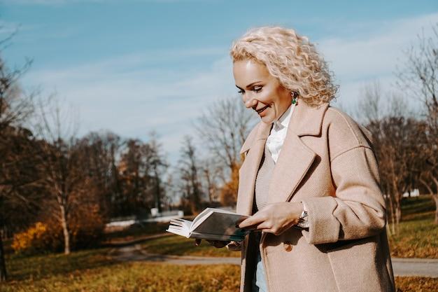 가을 코트에 여자는 책을 보유