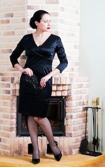 벽난로와 인테리어에 이브닝 드레스 여자