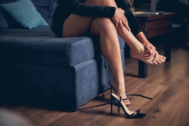 ベッドに足を組んで座っているイブニング ドレスの女性