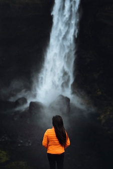 Женщина в оранжевой куртке у водопада хайфосс, исландия