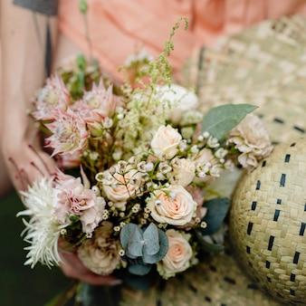 Женщина в оранжевом комбинезоне с букетом цветов