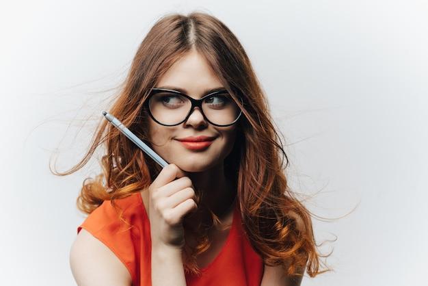 彼女の手にノートとペンを持つライトのオレンジ色のサンドレスの女性の学生