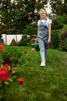 エプロンと手袋をはめた女性が庭にじょうろを持っています。女性の庭師は、屋外の植物、ガーデニングの趣味、花屋のライフスタイルの世話をします