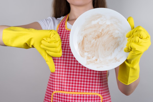 汚れた皿と指を押し下げるエプロンとゴム手袋の女性