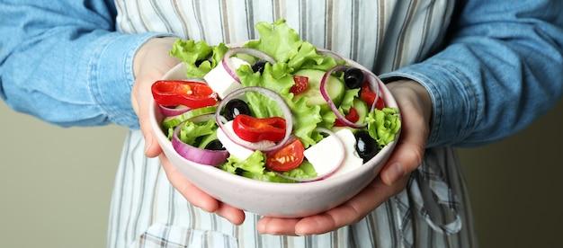 Женщина в фартуке держит миску греческого салата