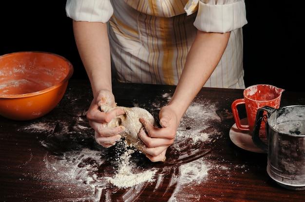 Женщина в фартуке месит тесто на старом деревянном столе