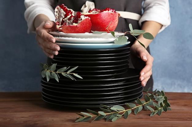 Женщина в фартуке со стопкой тарелок и гранатом за столом
