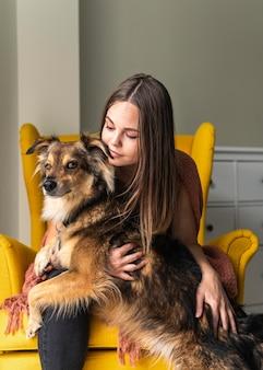 Женщина в кресле со своей собакой во время пандемии