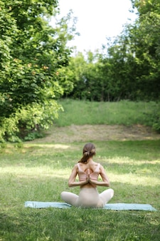 夏の緑の背景にアーサナヨガの女性。背面図