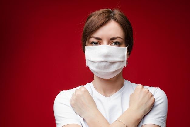 彼女の胸に組んだ腕を持つ無菌マスクの女性
