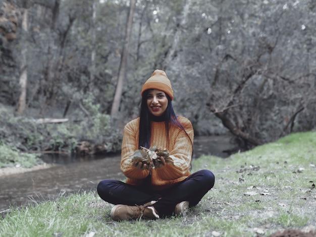 秋の服を着た女性、森の葉を摘む
