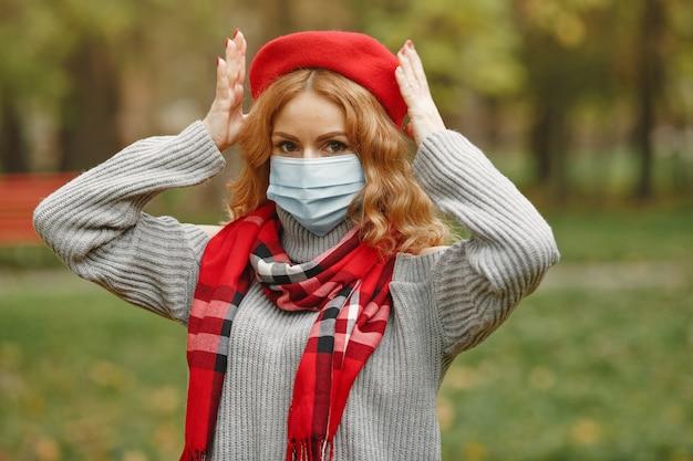 가 숲에서 여자입니다. 마스크에있는 사람. 코로나 바이러스 테마. 빨간색 스카프에 아가씨.
