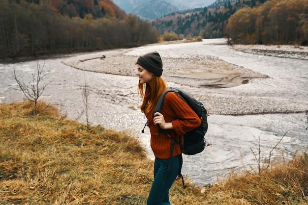 彼女の肩にバックパックを背負って山で秋の女性は観光川を旅行します