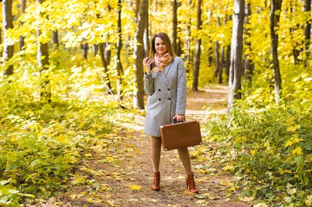 スーツケースでポーズをとって秋の公園の女性