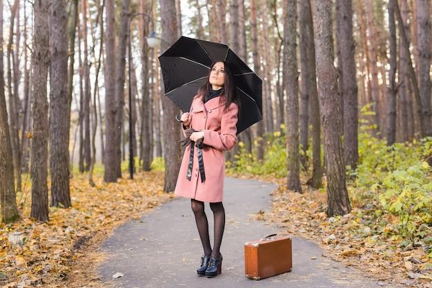 レトロなスーツケースと傘を持って歩く秋の公園の女性