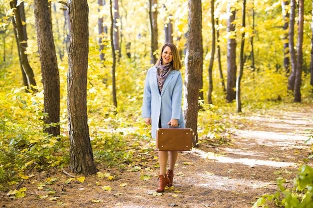 スーツケースと秋の公園ウォーキングの女性