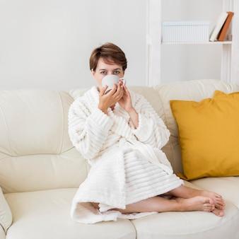 Женщина в халате пьет чай