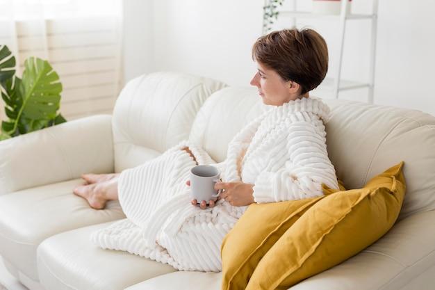 Женщина в халате держит чашку чая с длинным выстрелом